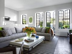 In the living room of designer Timothy Whealon's Manhattan apartment, steel French doors bring in the perfect amount of light. The sofa, inspired by a Billy Baldwin design and covered in a linen by Christopher Farr Cloth, and the cocktail table are custom designs, and an abaca rug by Merida tops chevron-patterned oak floors. Tour the rest of the home.   - ELLEDecor.com