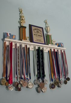 3 Ft White Award Medal Display Rack, accommodates 29 Lanyard Medals for Display, and a grooved Trophy Shelf to display trophies, plaques, and cased pin-style medals.For only $54.95 http://www.medalawardsrack.com/category/products/   2 Ft Award Medal Display Rack in Black. Showcasing Trophies,