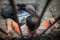 A Palestinian Christian man from Gaza tries to push the coffin of Jalila in a grave during her funeral on the small and overcrowded cemetery of the St. Porfirius Church, Gaza City, July 27, 2014.