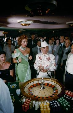 1955 fashion style found photo las vegas gambling roulette table woman lady mint green blue evening gown man in white suit cowboy hat 50s vintage