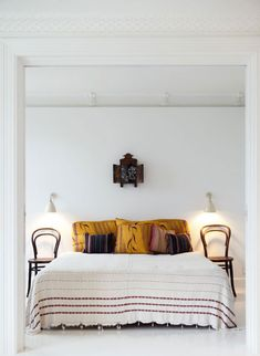 stark white bedroom combined with vintage bentwood cafe chairs and modern wall sconces, from bo bedre.
