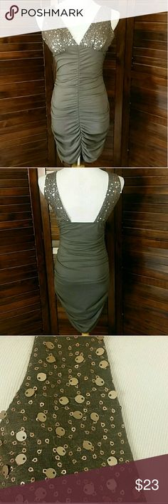 "Vavavoom!!! Sexy fitted, body conscious dress. Sequin plunge front with light pads (don't seem to be attached, they move around). Ruched body, high/low. Taupe color. Tag reads Large, please read measurements.  64% polyester/32% rayon/4% spandex 15"" across chest unstretched, approx 30"" long front, 38"" back.  This does stretch quite a bit. Color in Motion Dresses Mini"