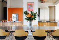Cozinha tem armário cor de laranja e balcão e cadeiras com madeira clara.
