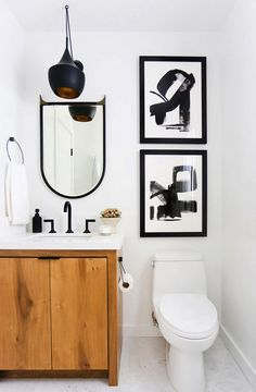Bright, small powder room with a modern black pendant light, black and white art, and a wooden vanity