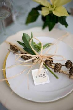 Simple place setting for the holidays. White plates with a few stems of greenery tied with twine