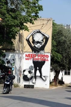 This political graffiti art states that the focus of most people in America and other popular developed countries, focus their money and leisure time on sports and entertainment, where in that time they spend, they could be helping those who need that time for help.