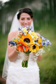 blue and yellow bridal bouquet with sunflowers and orange gerbera daisies