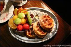有三個小巧可愛的圓形鬆餅跟一盅水果,還有附上糖漿跟奶水