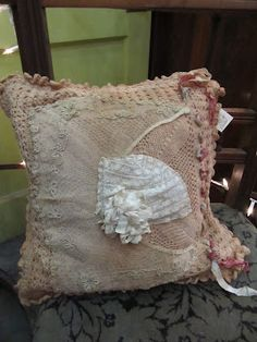 Pillow made with crochet, lace and a bonnet.