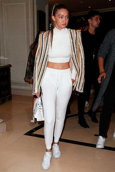 ELLE loves... Gigi Hadid arrives at the Balmain SS16 show in Paris wearing a white crop top and sweat-pant combo with a striped jacket and trainers.