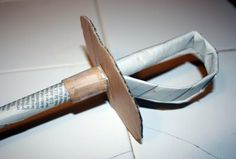 """Pirate sword. Use a full page of a news paper (really 2 pages). Roll diagonally. Tape closed. Flatten bottom third and fold toward """"blade"""" to make handle. Tape. We used old CDs for the hilts instead of cardboard and let the kids decoarte with sticky jewels."""