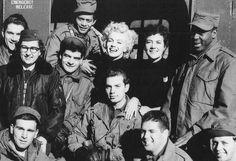 """Elle est ensuite invitée par les officiers du """"NCO Club"""" de la """"2nd Division"""" pour prendre un goûter. Au menu: gros gâteau de crème avec l'inscription """"Thank You Mrs MONROE"""", coupée par Marilyn, et café. Les soldats raconteront qu'elle avait un bon appétit. Marilyn n'a pas changé de tenue et porte toujours son pantalon kaki avec hautes rangers et pull noir. Jean O'DOUL, qui l'accompagne dans ses déplacements, est d'ailleurs vêtue de la même façon; et Marilyn lui a même prêté l'écharpe que la…"""