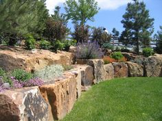 A stone wall created from rough cut rock creates an organic border. | Lifescape Colorado