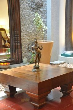 Brass Statue done right. Single piece on teak wood centre table. Let the Work speak for itself without a profusion of nick knacks ..