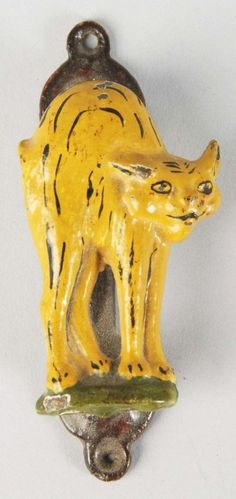 """The Tailless Cat Door Knocker"". Depicts bobtailed cat with arched back. Attributed to Greenblatt Studio."