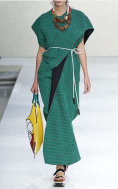 The 20th-anniversary collection embarks on a journey east with Marni's signature eccentric elegance. Oversized silhouettes resemble kimonos with cascading ruffles and sculptural folds, gracefully cinched at the waist with judo belts. The color palette moves from minimalist neutrals to vivid florals in full bloom.