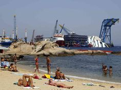 People sunbathe in front of the capsized Costa Concordia outside Giglio harbor, on Aug. 8.  ...