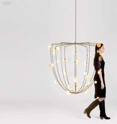 Bubbles on a fisherman's trap inspired Lindsey Adelman Studio's brass chandelier, Cherry Bomb Cage for Nilufar, festooned with handblown globes accented with gold foil.