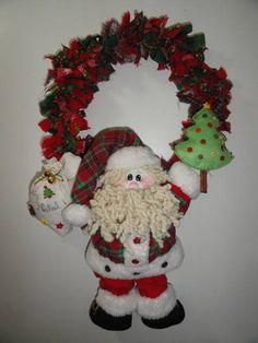 Papai noel com saco e árvore nas mãos e fixado numa guirlanda feita de retalhos de tecidos natalinos. R$ 100,00