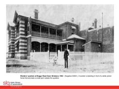 Warder's quarters at Boggo Road Gaol, Brisbane, 1903. A warder is standing in front of a white picket fence that encloses a small yard outside the quarters.