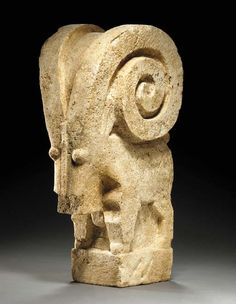 A SABEAN LIMESTONE IBEX   Circa 1st Century A.D.   Standing on an integral plinth, the stylized body articulated on three sides, with massive curving horns, small bulbous eyes, and a raised vertical line representing the nose, the square block below the head representing the beard, the pointed ears behind the horns, the animal perhaps serving as a basin support