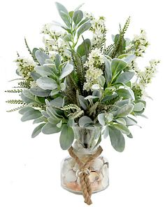 A generous gathering of Lamb's Ear leaf sprays, sword fern, and & white lilacs is beautifully arranged in a clear glass vase that is filled with assorted seashells and accented with rope.
