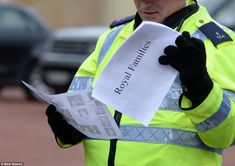 A policeman checks is crib sheet for the Royal Family as they arrive at the Queen's Christmas lunch at Buckingham Palace for her extended fa...