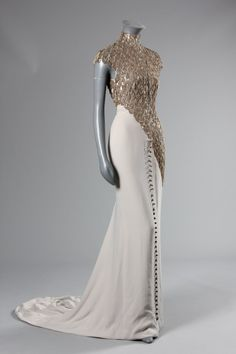 An Alexander McQueen for Givenchy chain-fringed grey crepe de chine evening gown, Spring-Summer haute couture collection, 1998, labelled P/E 1998. White organza bodice with diagonal band of scale-like silver chain loops descending diagonally from the high neck across the hips, the skirt front with metal bauble buttons, long trained skirt,