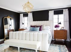 Farrow & Ball's Downpipe covers the walls of Mitchell's bedroom. A luxe tufted bed by Consort Design, rotating sconces by France and Son, and an angular pendant from Circa Lighting are reflected in a mirror from RH. The bench was found at Anthropologie, the rug is from Lawrence of LaBrea, and the pillows are from Consort Design.