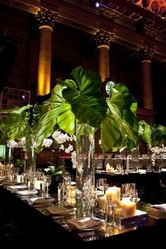 Lush, luxe, and romantic centerpieces of elephant ear leaves accented with white orchids.