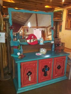 Turquoise mirror and matching cabinet with poppy red doors.  Rustic ranch design.