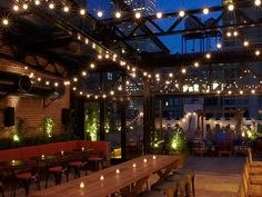 """No dating apps necessary: At this grand, industrial chic fusion of indoor- outdoor space, exposed brick, braided lights, a retractable glass roof, and the glow of the Empire State Building join forces to play Cupid. The strong cocktails—several of which come in """"caddies"""" with multiple servings—also help."""
