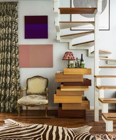 A 19th-century Italian armchair sits under the spiral staircase in the living room of this colorful Sâo Paulo Duplex. The stacked wooden dresser is by Raw Edges and Shay Alkalay for Established & Sons, the artworks are by Estela Sokol, and the poster is by Bridget Riley.