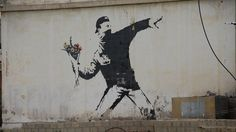 Rage, Flower Thrower by Banksy in Beit Sahur, Palestina, depicts a protester wearing throwing a bouquet of flowers