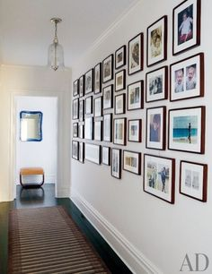 Family photos line a hallway in Tracy Pollan and Michael J. Fox's Manhattan home; the striped runner is from Doris Leslie Blau   archdigest.com