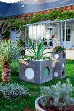 Jardinières en béton improvisées dans des regards de gouttières
