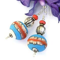 The vibrant red stripe that runs around the middle of the artisan made lampwork glass beads definitely  catches the eye.  It reminds me of a blazing flare from the setting sun against the mountains I