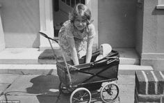 dailymail:  Princess Elizabeth playing with a doll in a toy pram outside the play house Y Bwithyn Bach, the miniature cottage in Royal Lodge given to the princess in 1933 for her sixth birthday by the people of Wales.