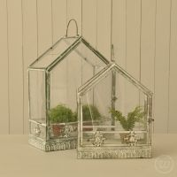 A set of two glass houses with a weathered finish
