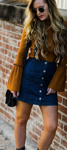 Mustard bell sleeve sweater styled with denim skirt overalls, and metallic booties