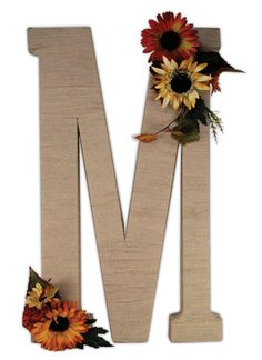 The large Paper Mache letter M was painted, wrapped in a brown yarn and then embellished with fall flowers. A perfect rustic, fall piece! Find more inspiration at http://www.craftsdirect.com/default.aspx?PageID=326.