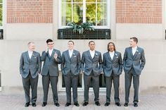 Groom and groomsmen in grey tuxedos with white bow ties for a Gatsy inspired wedding.