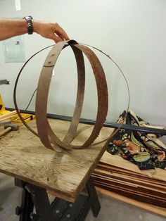 To start, you'll need three discarded whiskey barrel rings! As you can see, the top ring is in pretty rough shape, but that will work ju. Wine Barrel Crafts, Wine Barrel Rings, Wine Barrels, Whiskey Barrel Planter, Bourbon Barrel, Wine Barrel Furniture, Barrel Projects, Metal Barrel, Metal Garden Art