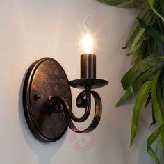 Romantically-curved wall light Caleb in a country house style Caleb has an oval wall mount, from which a spirally twisted arm leads to the light bulb, which is seated like a candle on a tray. The entire frame is made of metal and boasts an antique rust look. Mounted on the wall, a special elegance arises when Caleb is turned on, thus creating ambient light in the room. A variety of light bulbs can be turned into the E14 socket: Not only incandescent or halogen lamps are an option, but also…