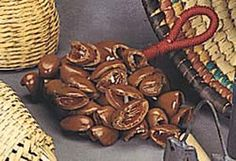 NUTSHELL HAND RATTLE - Rattles, or jingles, were commonly made from plant and animal materials. Usually worn about the body or attached to clothing, these instruments often provide a dancer's own accompaniment.   This NUTSHELL HAND RATTLE is woven together with string and attached to a rope handle. Authentic native instrument from Nigeria.