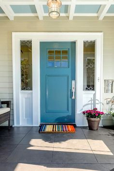 The Little Things - turquoise front door, pale blue ceiling, colorful mat and flowers make this entry stand out. From HGTV's Curb Appeal
