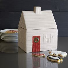 Our cozy log cabin cookie jar in warm winter white contains seasonal goodies with a homespun touch. Giving three-dimensional life to holiday artwork by Jenny Bowers, this earthenware cabin with roof lid and clever chimney handle features rustic detail including a welcoming wreath on the festive red front door. A clear silicone gasket on the inside lip of the lid ensures that your holiday cookies stay fresh.