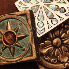 Our Compass Rose in Verdigris bronze tile with tiger eye jewel (left) and our acanthus medium in bronze (right) featured on Tile Designs of New England.