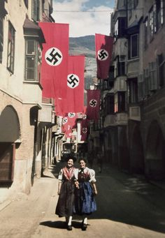 """In a private, original color photograph, two women walk down aof narrow street on a random """"banner day"""" in Nazi Germany."""