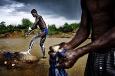 © @pepbonet_noor /#noorimages. #Diamond diggers washing themselves and their clothes under heavy rain at Sweet Mother's #Mine. #SierraLeone, 2008